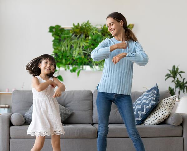 Mother and Daughter dancing in front of greenwall.